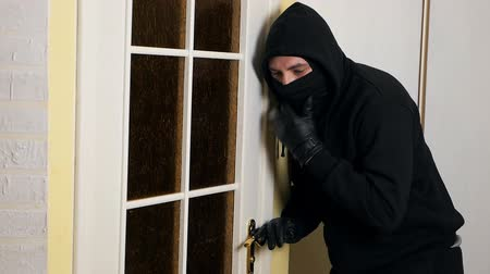 intruder : Burglar wearing a black mask and clothes at a crime scene. Spy in a residential building