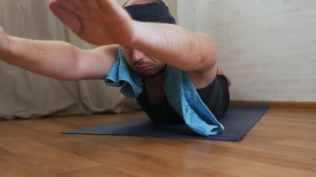professional wellness : Young bald brutal man tries to do yoga on the floor of his apartment