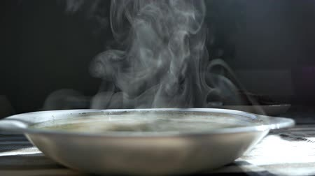 kluski : Chicken noodle soup - broth. Traditional chicken soup served in a bowl. Steam from a bowl of soup