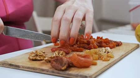 morele : A young housewife cuts dried fruit - dried apricots with a knife on a cutting board. Healthy eating concept