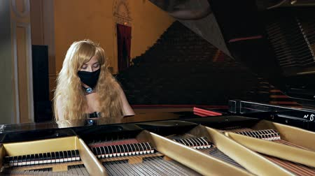 классический : A girl in a black dress and with a mask on her face plays the piano. Unusual musical performance Стоковые видеозаписи