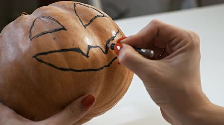 резать : Drawing a funny face on a pumpkin with a black marker.draw halloween pumpkin ready to carving