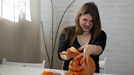 decorating : Woman in disgust prepares a pumpkin for Chloin, takes out seeds and pulp