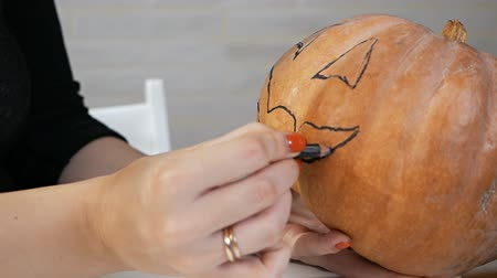 esculpida : Drawing a funny face on a pumpkin with a black marker.draw halloween pumpkin ready to carving
