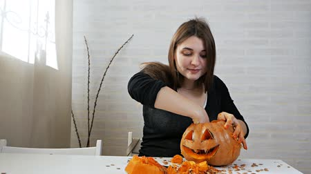 A woman prepares a pumpkin for Khlloin, takes out seeds and pulp