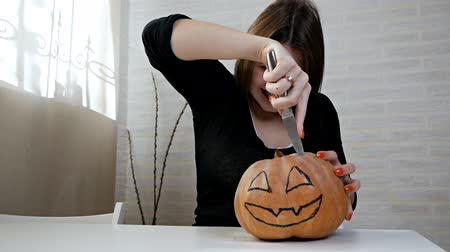 outubro : Woman with a crazy look and stare, preparing a pumpkin at a Halloween party on the kitchen table, a girl cuts out her mouth with a knife