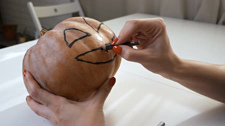 準備する : Drawing a funny face on a pumpkin with a black marker.draw halloween pumpkin ready to carving