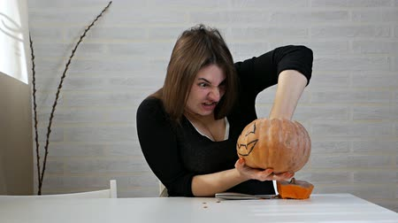 Woman fooling around with carved pumpkin ready for Halloween