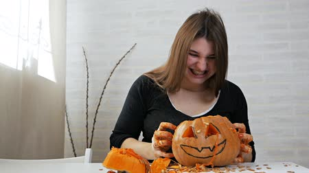 outubro : Orange pumpkin carved for the celebration of Halloween. A woman with a crazy look takes out seeds and pulp from a pumpkin. Preparing the scenery for a traditional fall party. Crazy halloween Stock Footage