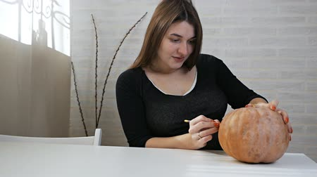Halloween concept, happy girl sitting at a table with pumpkins, painting eyes and mouth on a Halloween pumpkin