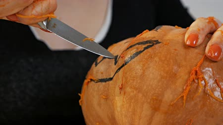 outubro : Woman carves from a pumpkin Jack-o-lantern for Halloween celebration Stock Footage