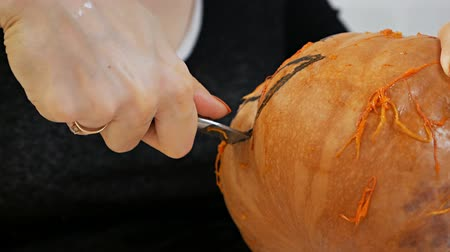 Woman carves from a pumpkin Jack-o-lantern for Halloween celebration Wideo