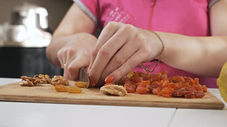 A young housewife cuts dried fruit - raisins with a knife on a cutting board. Healthy eating concept. Slow motion