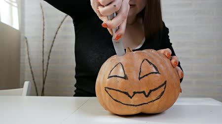 Orange pumpkin carved to celebrate Halloween tradition with woman hands. Preparing the scenery for a traditional fall party