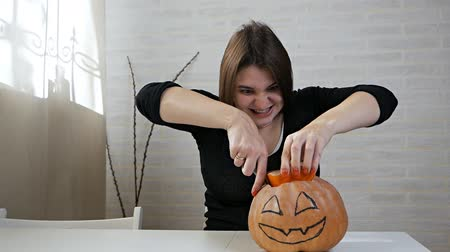 Woman with a crazy look and stare, preparing a pumpkin at a Halloween party on the kitchen table, a girl cuts out her mouth with a knife