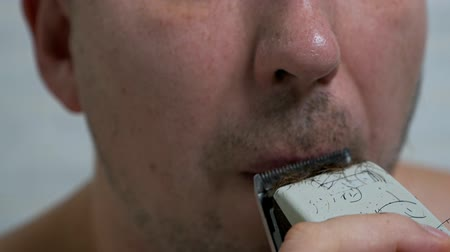 A man shaves his beard and mustache with an electric razor at home, hair removal in front of a mirror. Mens care