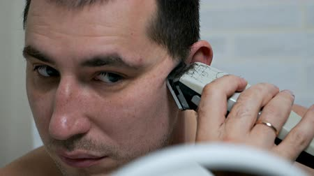 shaver : A man shaves his beard and mustache with an electric razor at home, hair removal in front of a mirror. Mens care
