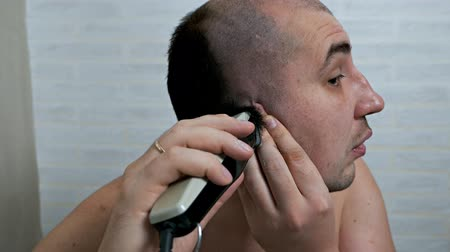 The guy shaves his head with a razor. Hair removal at home Wideo