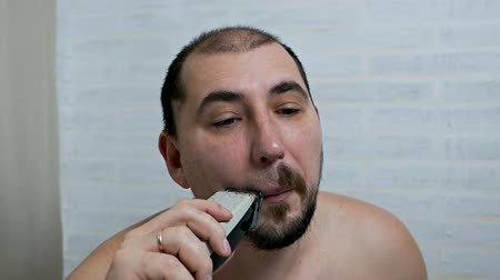 бритье : A man shaves his beard and mustache with an electric razor at home, hair removal in front of a mirror. Mens care