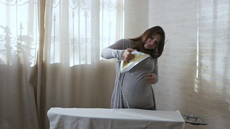 A young pregnant woman is trying to iron, but the iron is not working. Housework