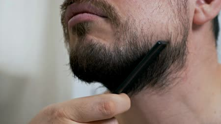 The concept of skin care. A man with a beard or an unshaven guy takes care of his appearance in front of a mirror Wideo