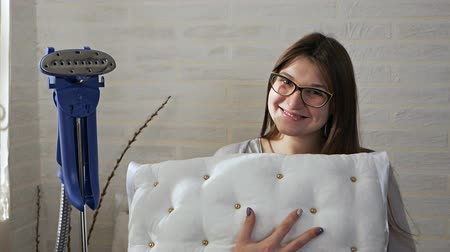 гладильный : Cute young woman holds a pillow in her hands and flirts playfully. In the background is a steamer