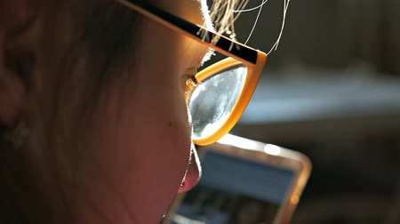 Side view of a young woman with glasses looking at a smartphone near the window