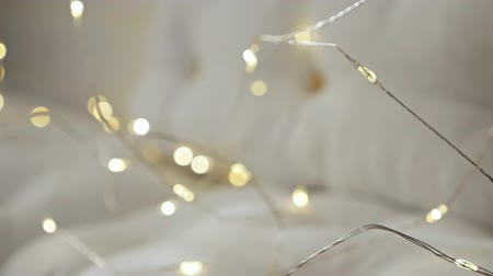 A white sofa with cushions is decorated with holiday lights.Christmas decorations for celebration