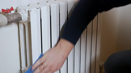 šedé pozadí : Radiator on a wall. A male hand cleans a heating radiator. Cold, winter, heating, house Dostupné videozáznamy