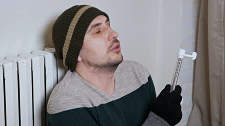 sistemas : Man checking the temperature of the heating battery. Cold winter, cold in the house, apartment. A man warms himself near a heating battery