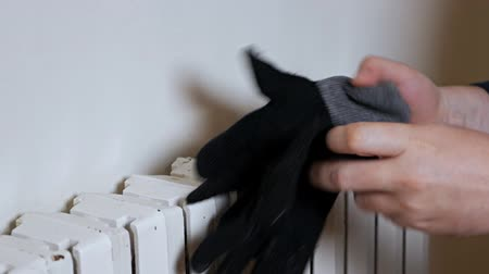 A man in a hat warms his hands on a heating radiator near the wall. Cold in the apartment, poor heating system
