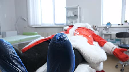 mókás : A handsome middle-aged man in a Santa costume is lying in the hospital, feeling tired and headache. The concept of stress and frustration. Santa Claus is sick in the hospital Stock mozgókép