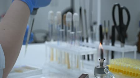 The creation of a biological drug that provides activation of acquired immunity to a specific disease. Female researcher using test tubes to fill a micropipette in a large modern laboratory