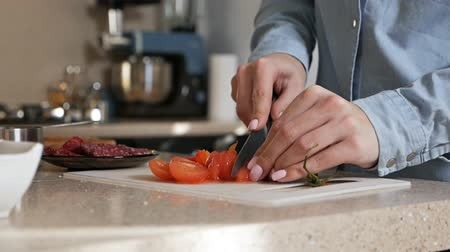 biber : The girl cuts with a knife a ripe juicy tomato. Slicing fresh vegetables for pizza Stok Video