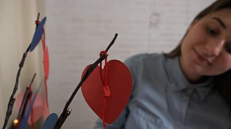 composição : card for valentines day with text happy valentines day.Valentine.Young attractive girl made decorations in the form of a heart tree for Valentines Day Stock Footage