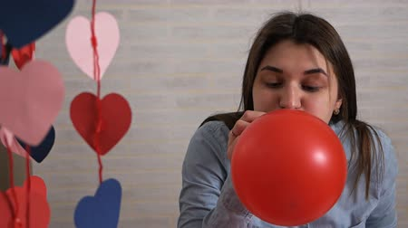 têxteis : Attractive young woman inflates balloons at home preparing for the holiday, Valentines Day