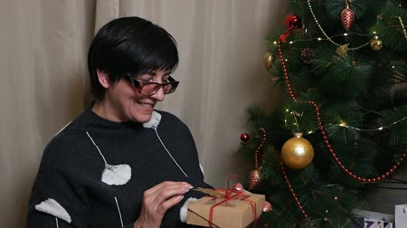 noel ağacı : Woman aged with a Christmas present at the Christmas tree Stok Video