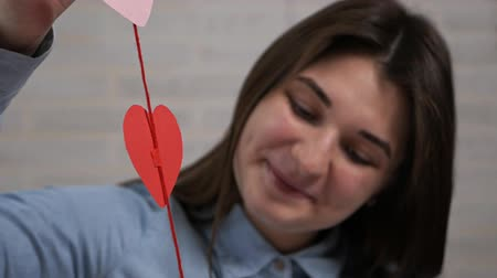 ラッピング : Young attractive girl made preparing heart decorations in an apartment on Valentines Day