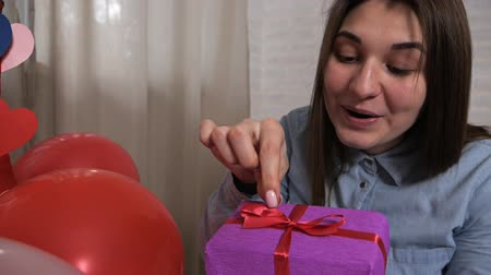 Валентин : A smiling woman holds a gift box and pleases, thinks that there. Valentine concept Стоковые видеозаписи