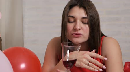 失望 : A beautiful girl in a red dress alone at the table drinks wine from a glass while intoxicated. Lonely valentine 動画素材