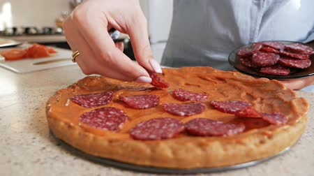 kiełbasa : Girl puts pieces of sausage on homemade pizza in kitchen Wideo