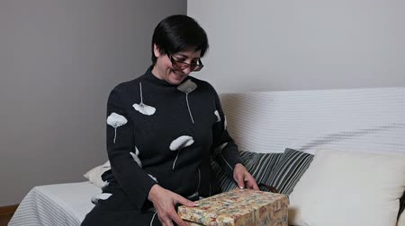 oturur : Surprised senior woman opening a gift box with admiration at home. A woman opens a gift box, sits on a sofa at home, happy with a gift Stok Video