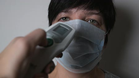 longontsteking : The appearance of symptoms of coronavirus. A woman measures the temperature with an electronic thermometer. The spread of the virus Covid-19.