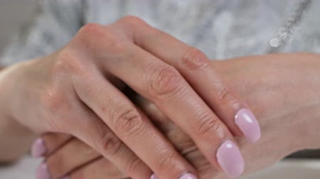 krem : Woman aged puts cream on her hands, a natural product for skin care at home Stok Video