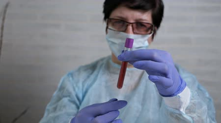 gyógyszerek : Female doctor doing experiments in a laboratory holding a blood test beaker