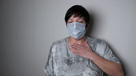 epidemia : The appearance of symptoms of coronavirus. A woman measures the temperature with an electronic thermometer. The spread of the virus Covid-19.