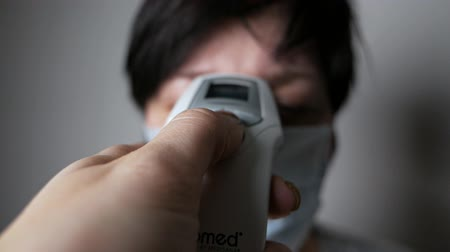 tosse : The appearance of symptoms of coronavirus. A woman measures the temperature with an electronic thermometer. The spread of the Chinese virus Covid-19.
