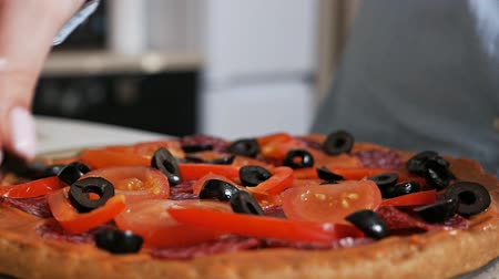 kiełbasa : Cooking Italian pizza at home, a girl puts olives on pizza