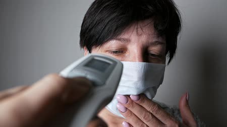 tosse : The appearance of symptoms of coronavirus. A woman measures the temperature with an electronic thermometer. The spread of the virus Covid-19.