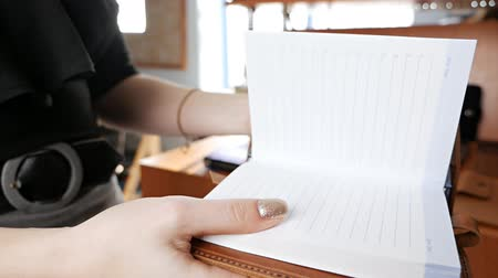 broszura : Leather diary, notebook demonstration in the hands of a woman. Leather workshop